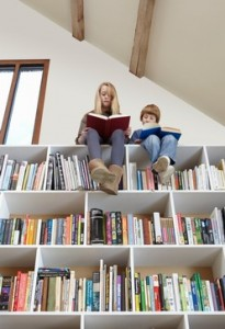 Children sitting on top of bookshelves